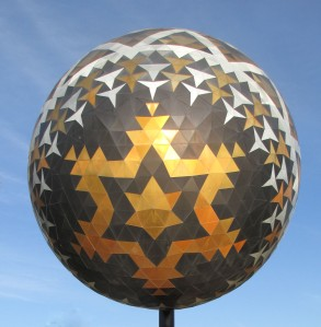 The radiating star on the lower end of the egg seems to not only symbolize life and goof fortune but to be shooting it down to earth.
